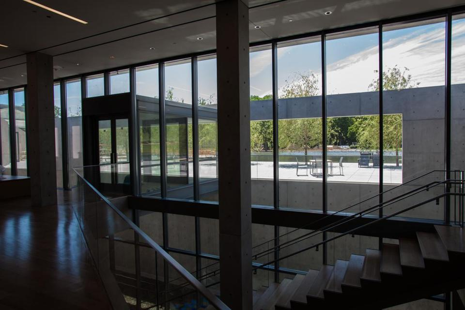 From inside the Center, one sees the pool beyond a sitting area, and stairs to galleries below ground.