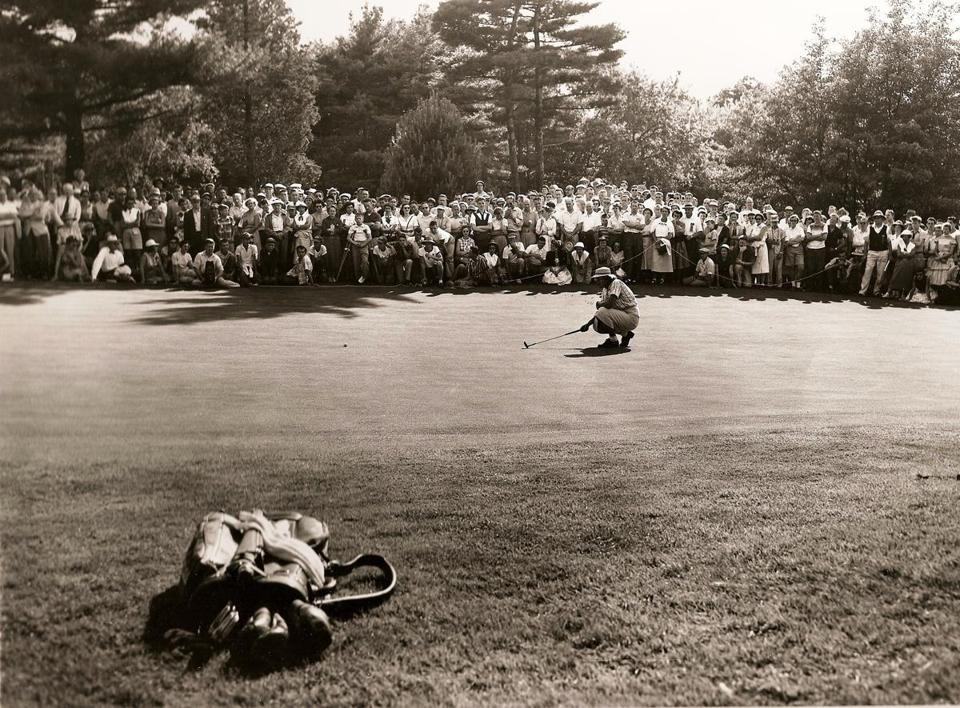 As a gallery throng watches, Babe Zaharias lines up a putt on the final hole  of the 1954 US Open, held at the Salem Country Club.