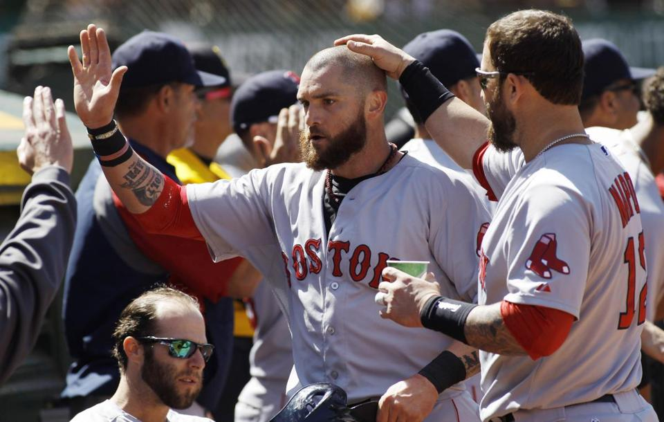 Jonny Gomes, who had a two-out, two-run hit earlier, is greeted after scoring on a triple in the eighth. George Nikitin/Associated Press