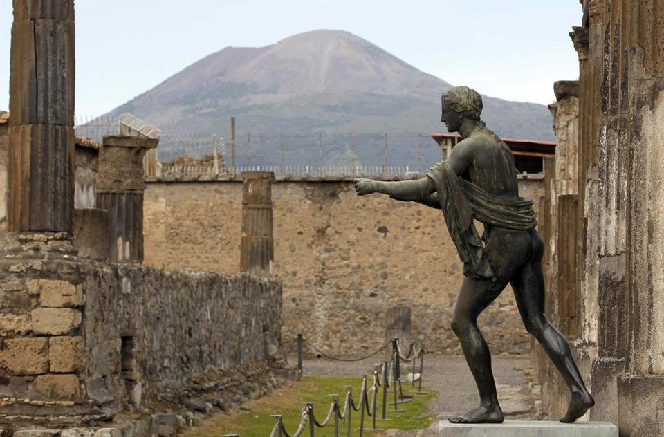 A statue in Pompeii, with Mount Vesuvius in the distance, often smoking.