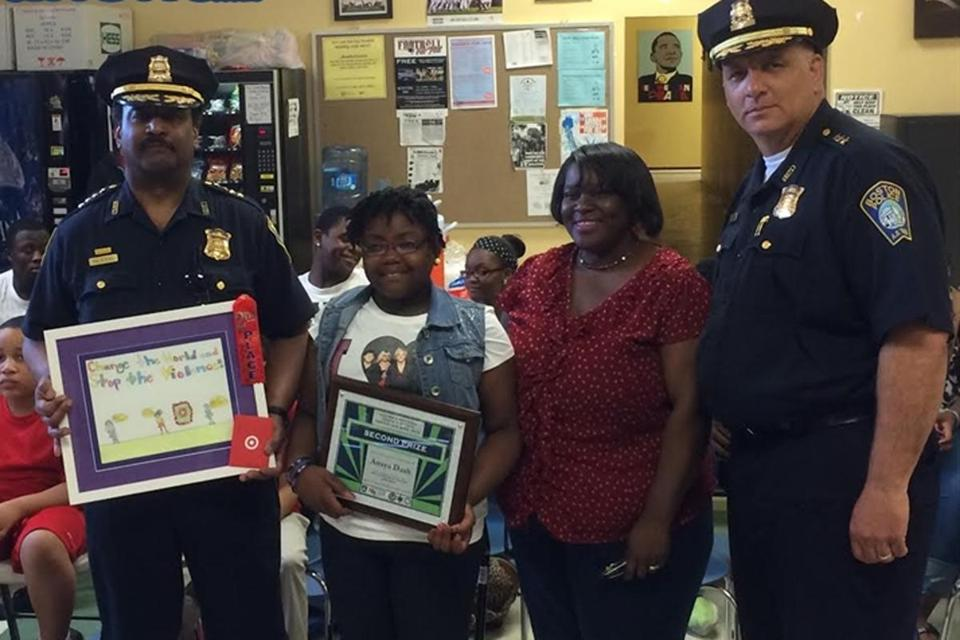 BPD Superintendent Randall Halstead and Deputy Superintendent Dennis White presented the Second Place Award in the youth violence prevention week poster contest to 4th grader Anaya Dash.