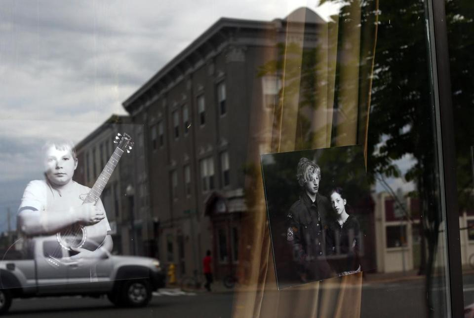 The window of Matt Kim's Academy of Rock reflects a downtown streetscape of Greenfield.