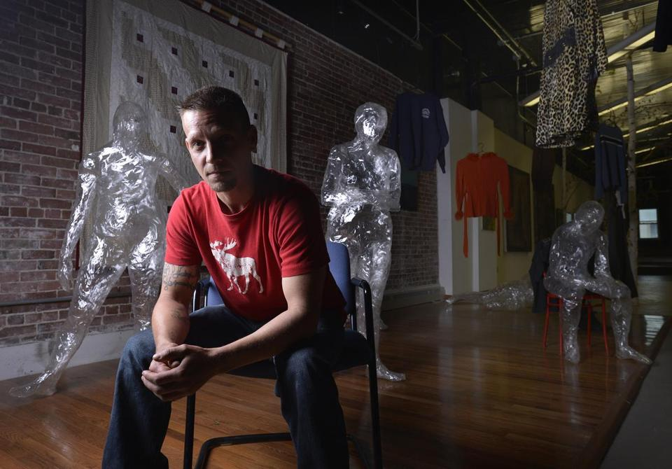 "Shawn Dobson, a recovering addict who has received help from Grace Street Services, is pictured surrounded by an art piece called ""Poppy Fields of Maine,"" which displays human figures made of adhesive tape and clothing from drug overdose victims who have died."