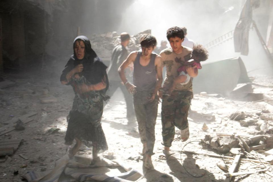 A woman and youths, one carrying a wounded baby, fled the site of a bomb attack in the city of Aleppo on Thursday.