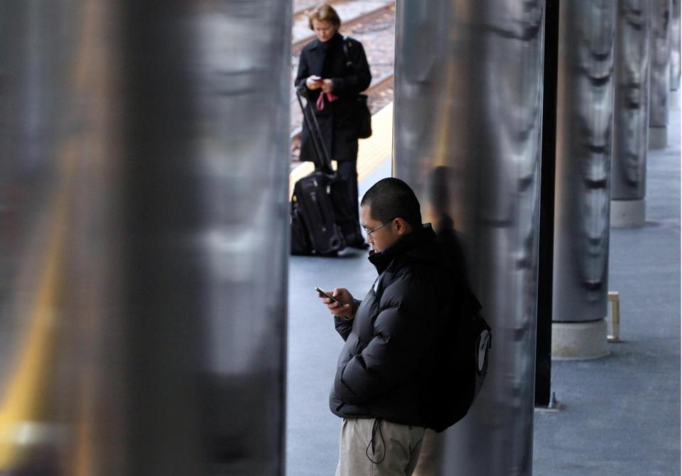 Youki Ohkami of East Boston checks his phone while he waits for the train in East Boston last November.