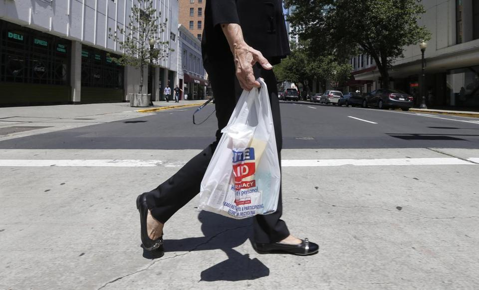 A woman walks with a plastic bag in Sacramento, Calif.