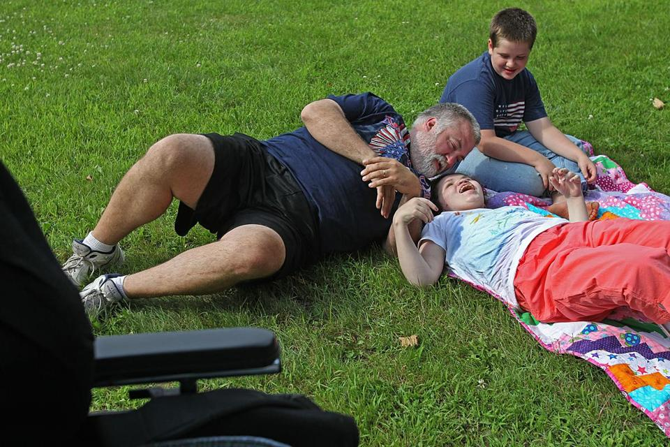 Haleigh played on the front lawn with her adoptive father, Keith Arnett, and brother, Jacob. The Arnetts first took Haleigh in as a foster child.