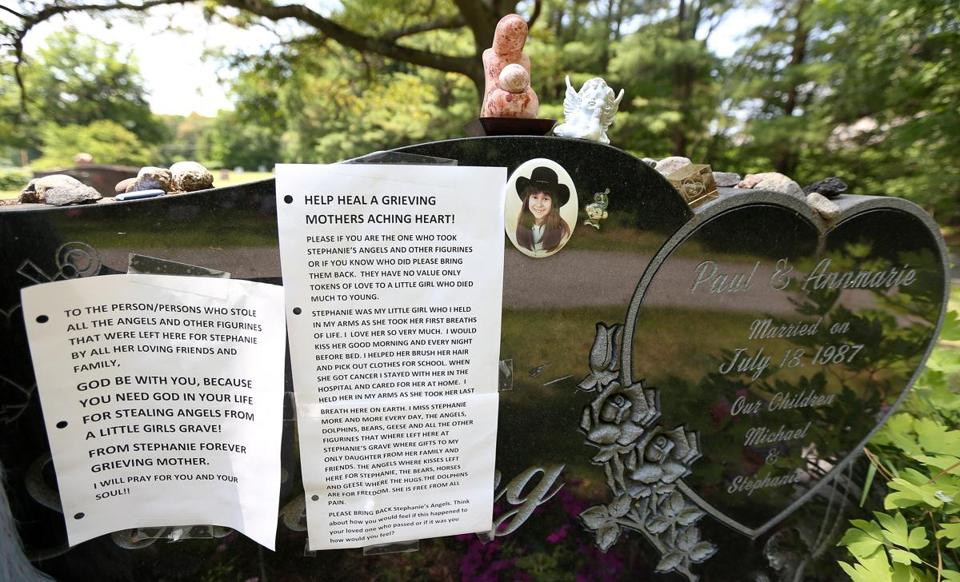 Annmarie Schieding posted this printed note Friday, the day after she noticed that angels and other figurines were removed from her daughter's grave.