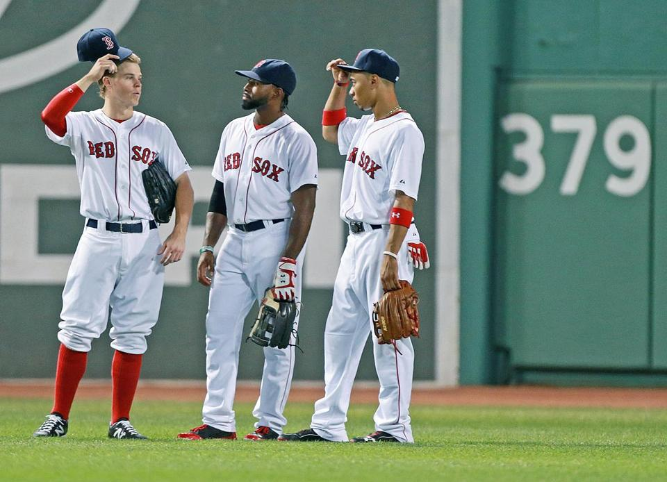 07/01/14: Boston, MA: Brock Holt, left, Jackie Bradley, Jr., center, and Mookie Betts, right, became the first three rookies to start a game together in the outfield (before September 1st callups) since Todd Benzinger, Ellis Burks and Mike Greenwell did it in 1987. They are shown during as pitching change chatting in center field. The Boston Red Sox hosted the Chicago Cubs in an inter league MLB game at Fenway Park. (Jim Davis/Globe Staff) section: sports topic: Red Sox-Cubs (1)