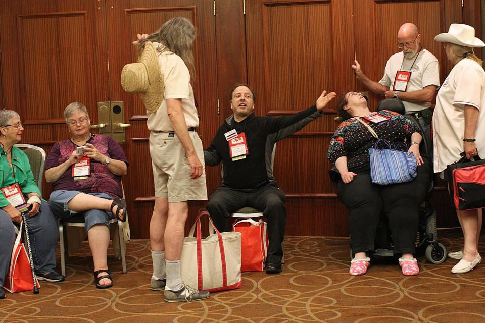 Bill Hecker of Leominster (center, seated), greeted JD Moore of Somerville, as the Mensa convention got undeerway.