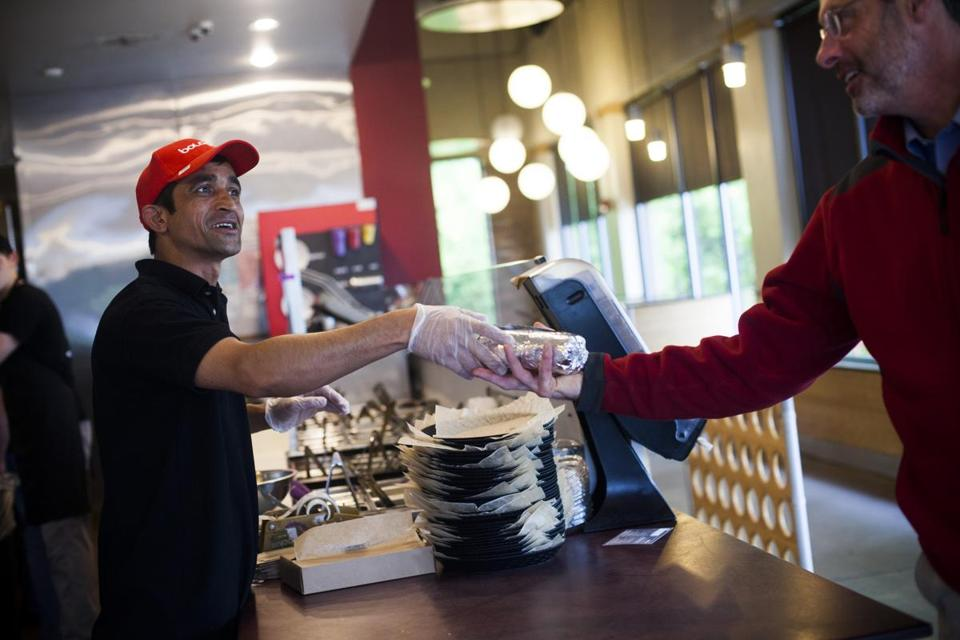 Ghana Shyam Khatiwada handed a burrito to a customer at a Boloco in Concord, N.H. Restaurants like Boloco that offer their employees above-average pay say they have lower turnover and better customer service.