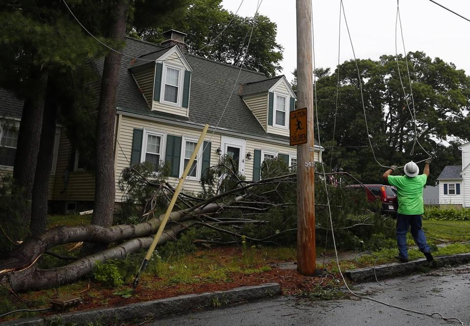A National Grid employee worked to repair downed power lines on Emery Street after a microburst hit Methuen Friday.