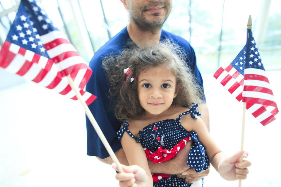 Camila Colón settled into the arms of her father, Michael, and waited as her mother, Yuderca, became a US citizen.