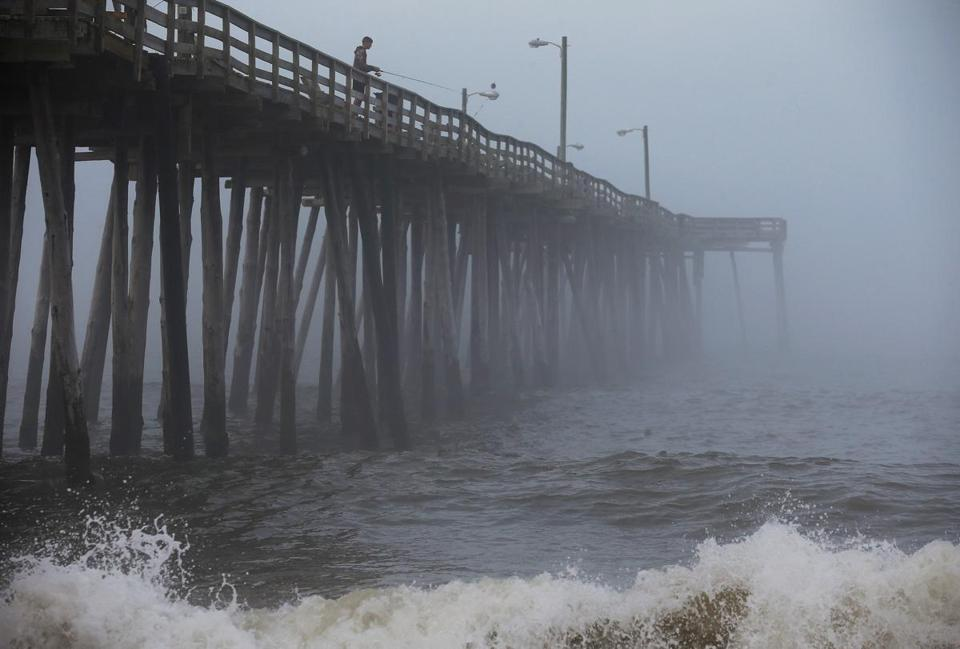 A man fished from the Nags Head Pier in North Carolina as fog and heavy surf rolled in ahead of Hurricane Arthur.
