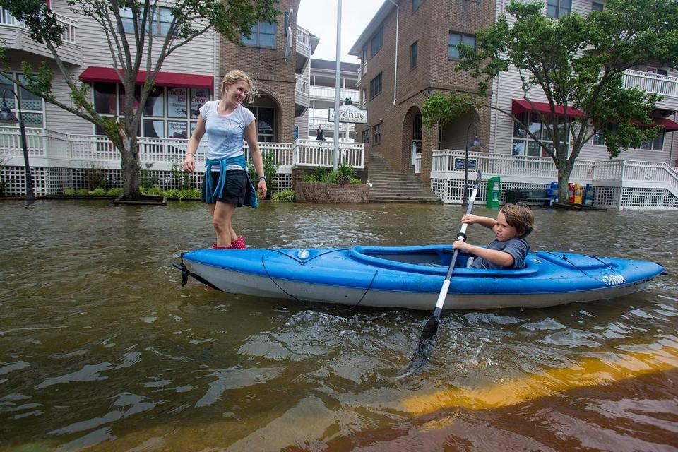 Lauren Heesemann, left, smiles at her nephew Summit Gibson, 7, from Oklahoma as he tries to maintain his balance on the kayak through a flooded street in Manteo, N.C.