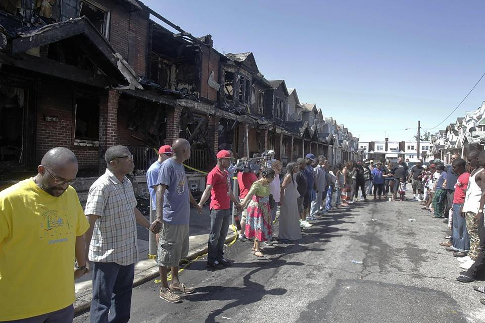 Members of the community formed a prayer circle in front of burned rowhouses on Saturday. The fire killed four children, including a baby.
