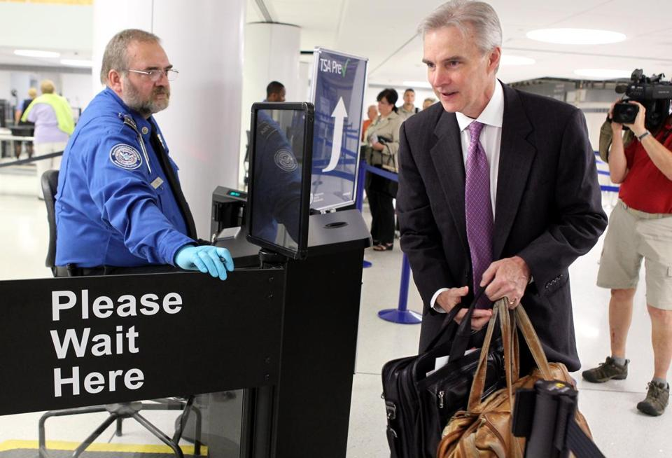 Transportation Security Administration agent Kevin Effan, left, allowed a screened passenger to board his American Airlines flight via the TSA PreCheck lane at Lambert-St. Louis International Airport.