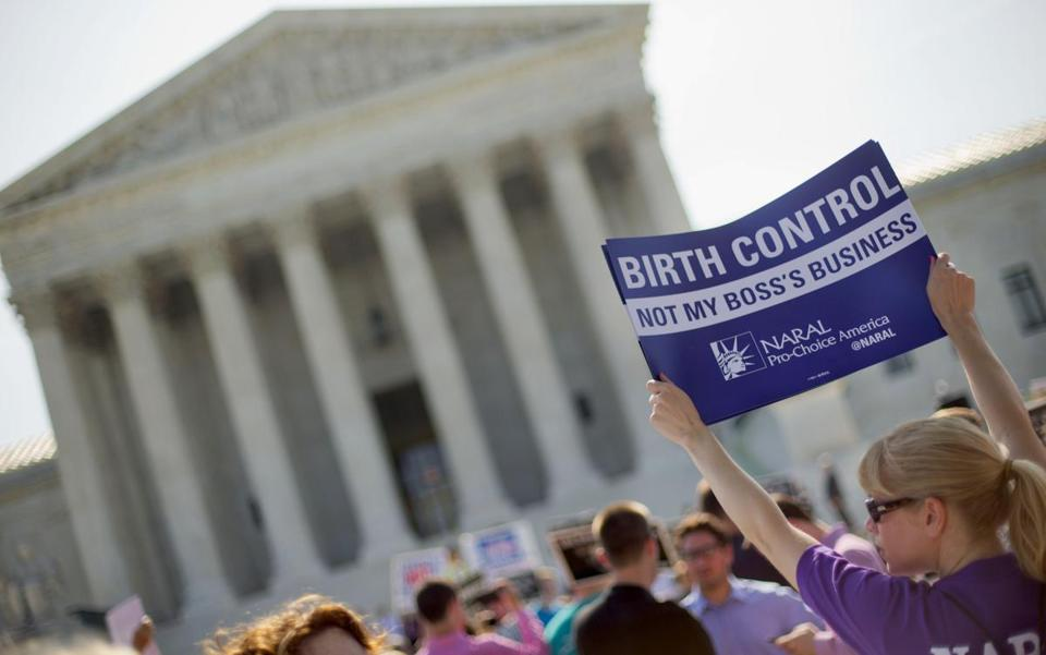 A demonstrator held up a sign outside the Supreme Court in Washington on the day the court decided in the Hobby Lobby case to relieve businesses with religious objections of their obligation to pay for women's contraceptives.