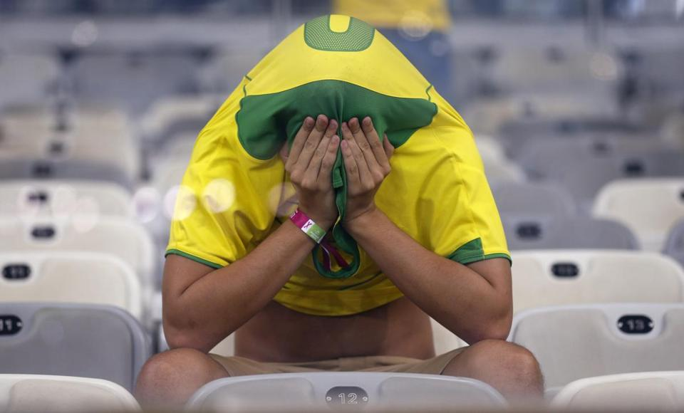 A Brazil fan covers his face after Germany's 7-1 victory in their World Cup semifinal. (Frank Augstein/Associated Press)