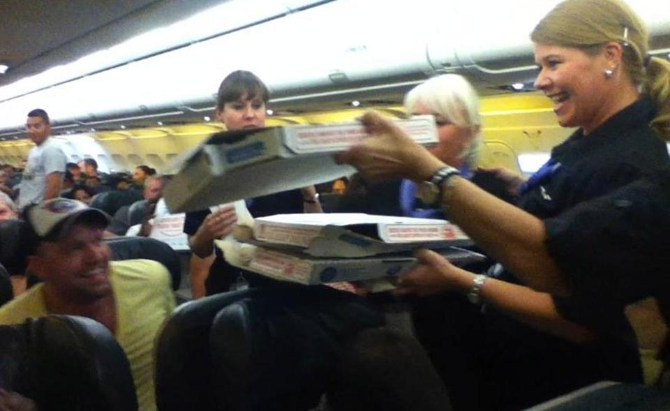 A Frontier Airlines flight attendant passes out pizza to passengers aboard a Denver-bound flight diverted to Cheyenne on Monday. The plane's pilot treated his passengers to the pizza after they were diverted.