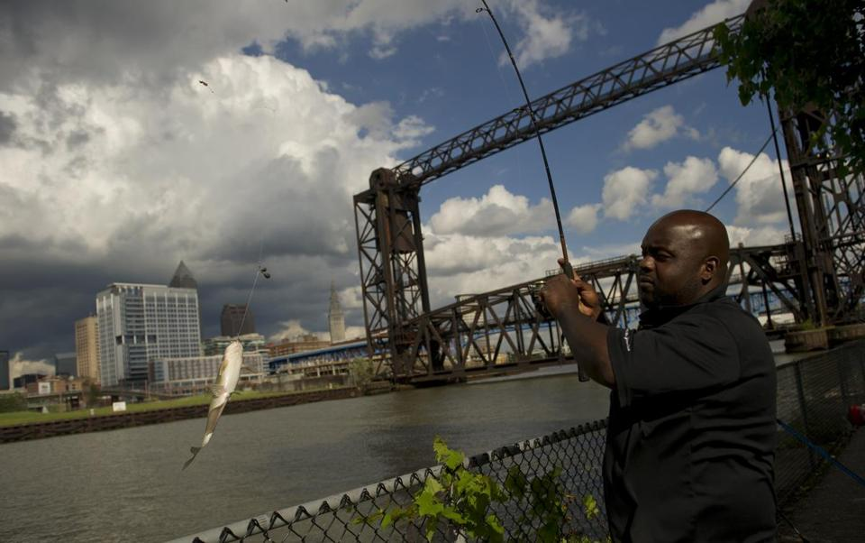 A man fished Tuesday in the Cuyahoga River with downtown Cleveland in the background.
