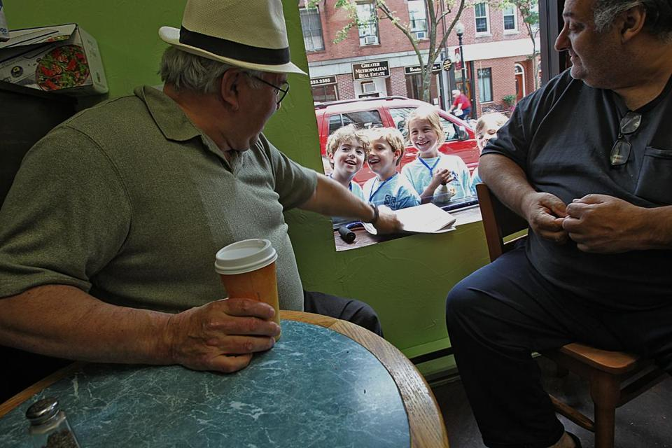 Johnny Cammarata (left) and Joey Buceta had coffee at My Cousin's Place on Hanover Street as summer campers looked on through a window.