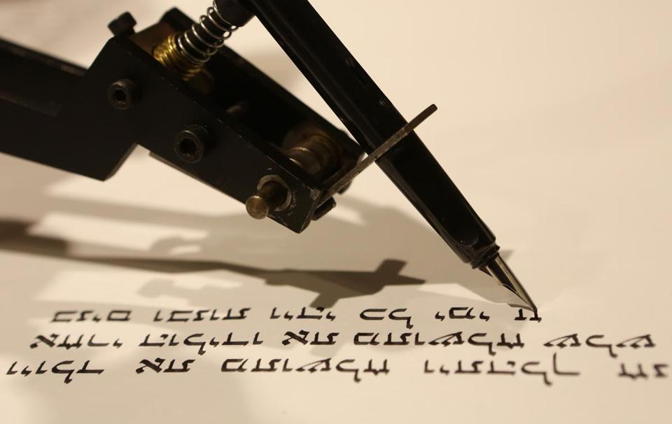 A robot writes down the Torah much faster than a human, but the work cannot be used in a synagogue.