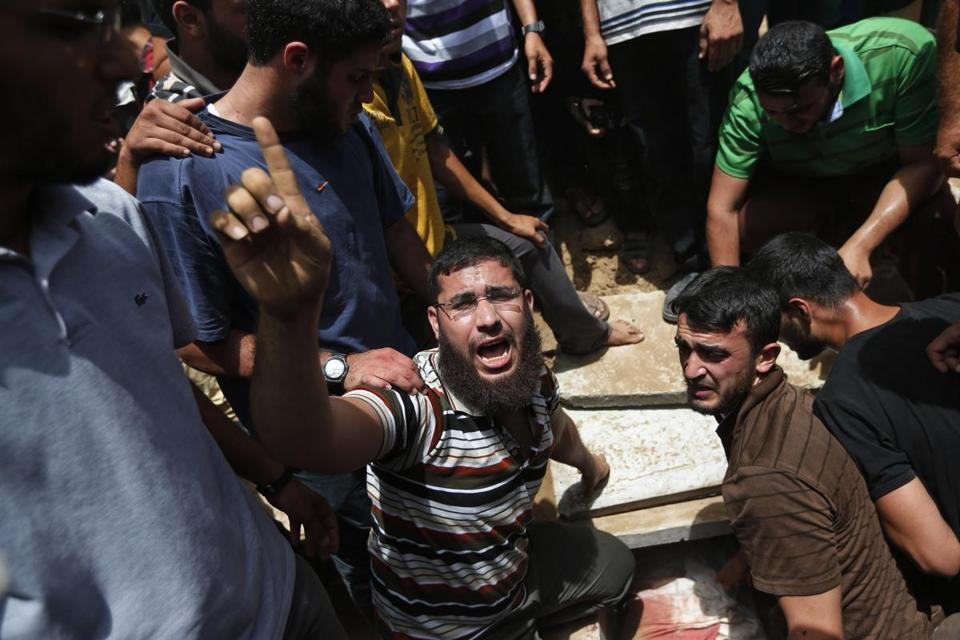A Palestinian mourner chanted slogans on the grave of a family member of the Gaza police chief.