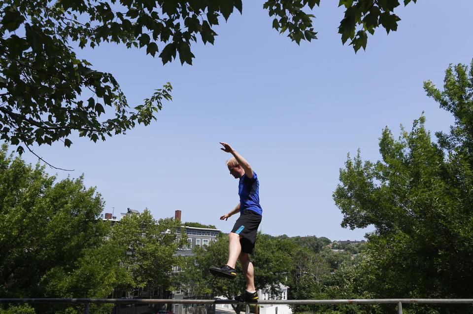 Mike Jones, 31, of Brookline balances on a railing during an outdoor Parkour class in Somerville.