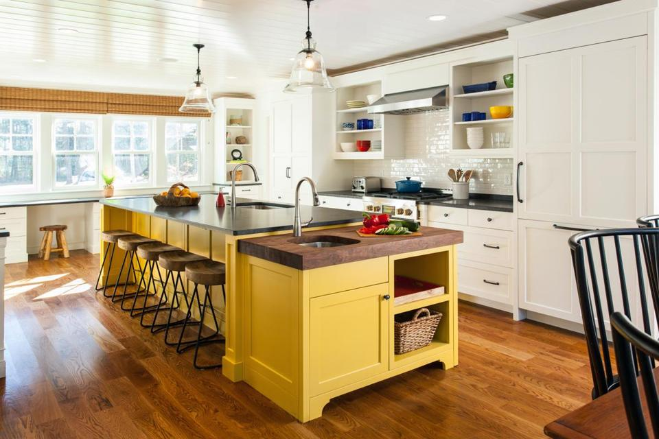 A sunny yellow island is the focal point of the Maguire family's kitchen on Scraggy Neck, in the Bourne village of Cataumet.