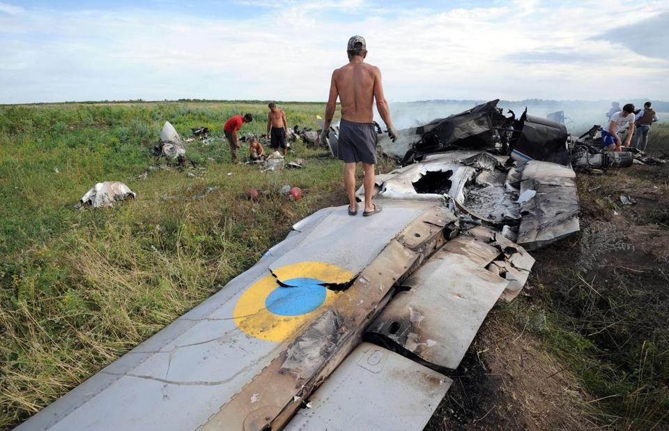 Villagers of Davydo-Mykilske, Ukraine, near the Russian border, rushed to the scene of a downed AN-26 transport plane to see whether they could collect parts from the wreckage.
