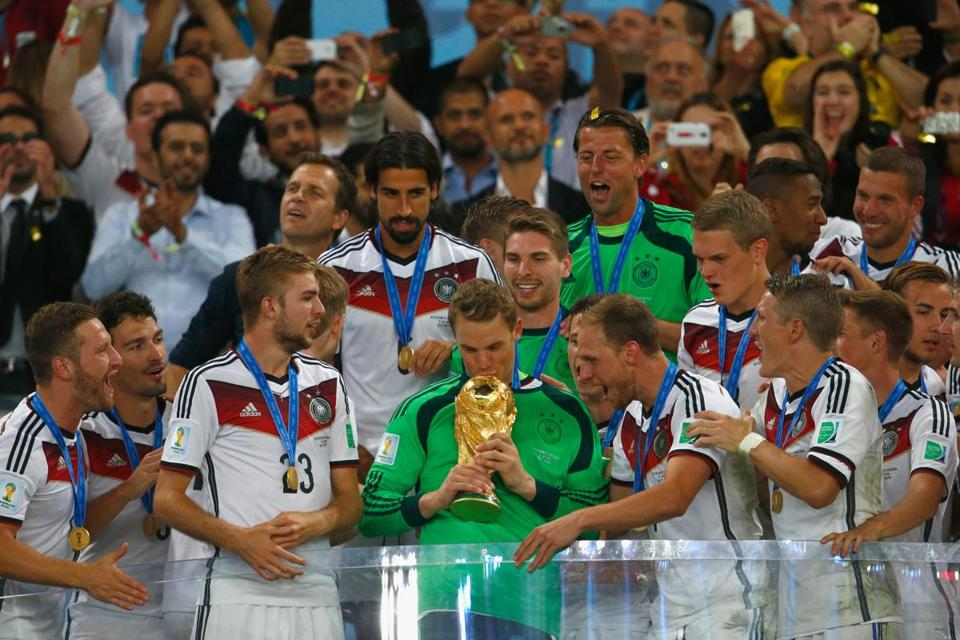 Keeper Manuel Neuer of Germany kisses the World Cup trophy with teammates after defeating Argentina 1-0 in extra time.