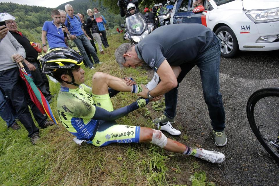 Two-time race winner Alberto Contador is assisted during Stage 10 following a crash that knocked him out of the Tour de France. (AP Photo/Christophe Ena)