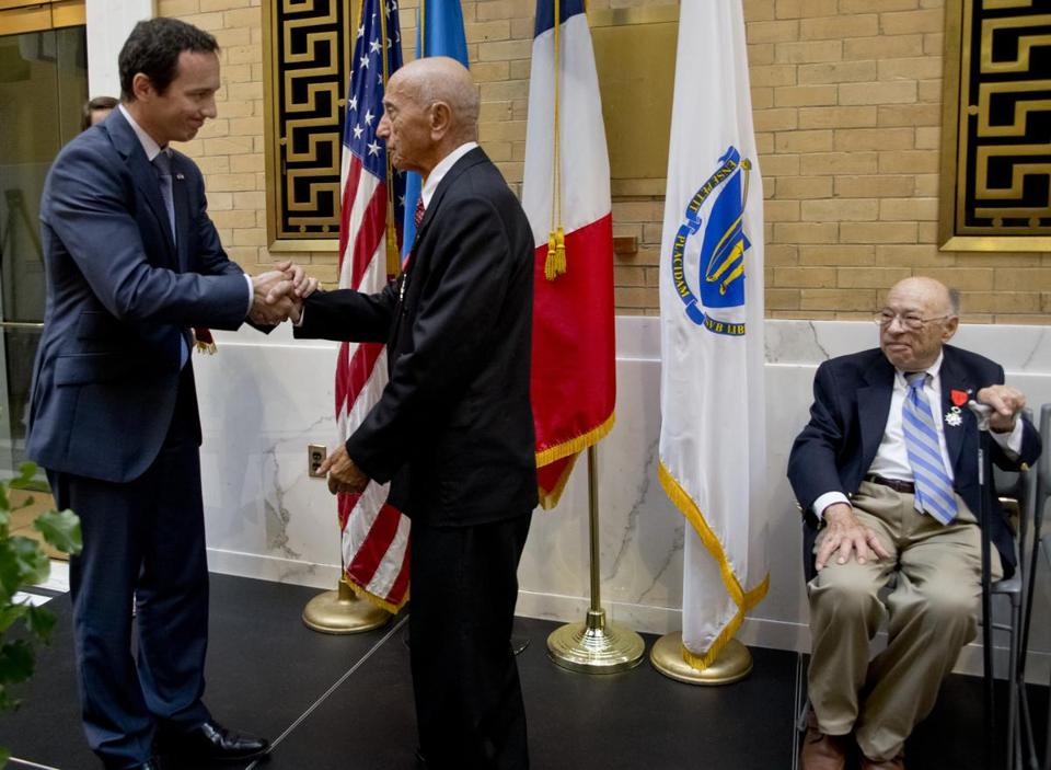 Boston, MA 7/14/2014 Fabien Fieschi (cq),left, Consul General of France in Boston shaking hands with Frank Pagliuca (cq) after Pagliuca (midde) and Norman Grossman (cq)(seated) were awarded the French Legion of Honor for their service in World War ll at the State House on Bastille Day on Monday July 14, 2014. (Matthew J. Lee/Globe staff)