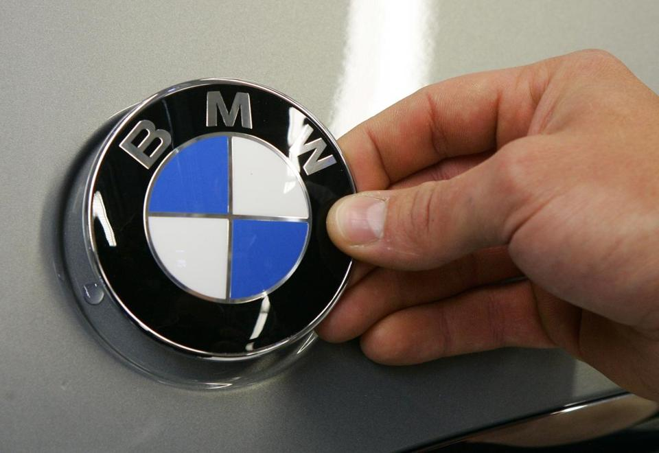 A worker attached a BMW company car logo on a new 3-Series car at the company's plant in Leipzig, Germany.