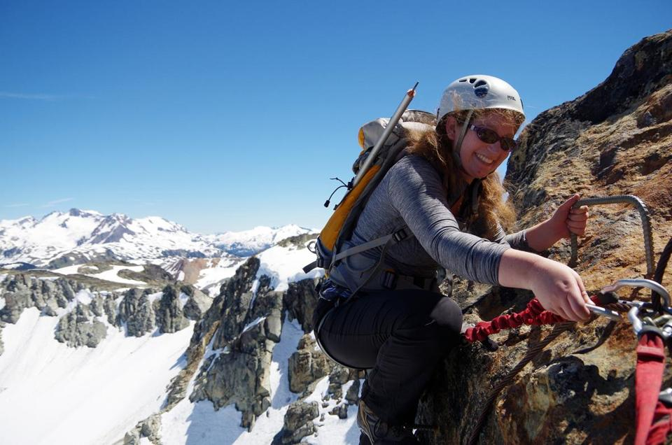 Rachel Weber of San Francisco, scrambles onto a ledge at the top of Whistler Peak after climbing 660 vertical feet on Whistler's Via Ferrata route.
