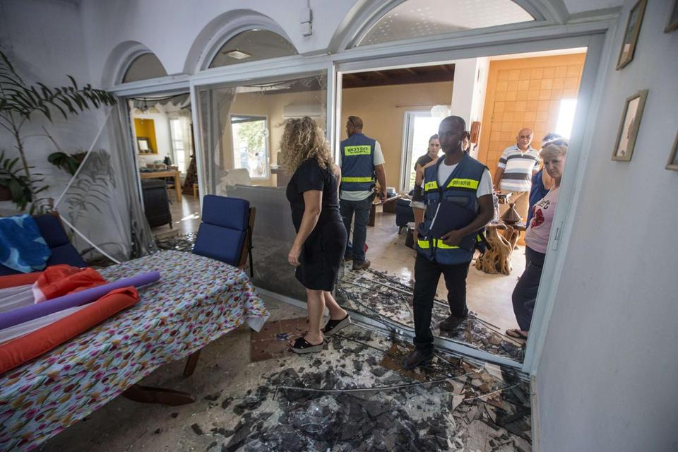 Emergency workers and Israeli security check a house damaged by a rocket fired in Ashkelon on Wednesday.