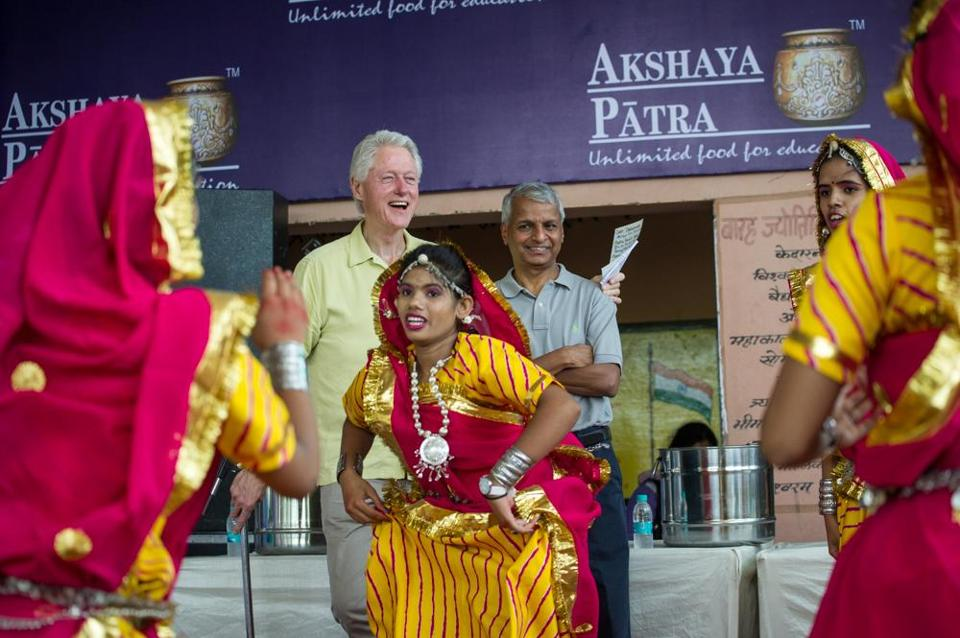 Gururaj Deshpande (center above and below) joined former President Bill Clinton in Jaipur, India, meeting students fed by Akshaya Patra kitchens.