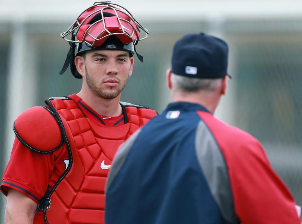 02/25/14: Ft. Myers, FL: FOR POSSIBLE USE WITH BASEBALL PREVIEW SECTION.........Red Sox catching prospects Blake Swihart (left), and Christian Vazquez (right) are pictured talking to bullpen coach Dana LeVangie (center). (Jim Davis/Globe Staff) section:sports topic:Red Sox Spring Training
