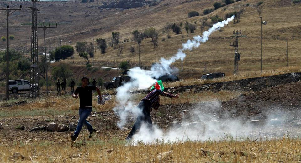 Palestinian protester returns a tear gas grenade at Israeli soldiers near the West Bank city of Nablus. Alaa Badarneh Photo