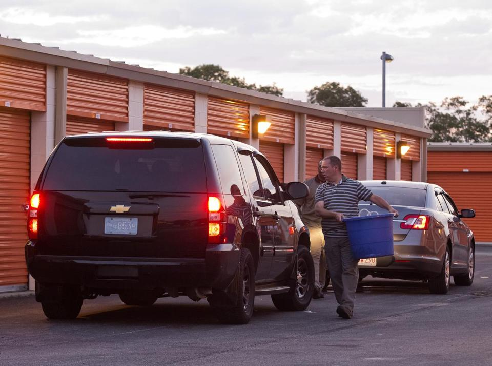 State officials loaded evidence into a vehicle from a Weymouth storage facility on Thursday.