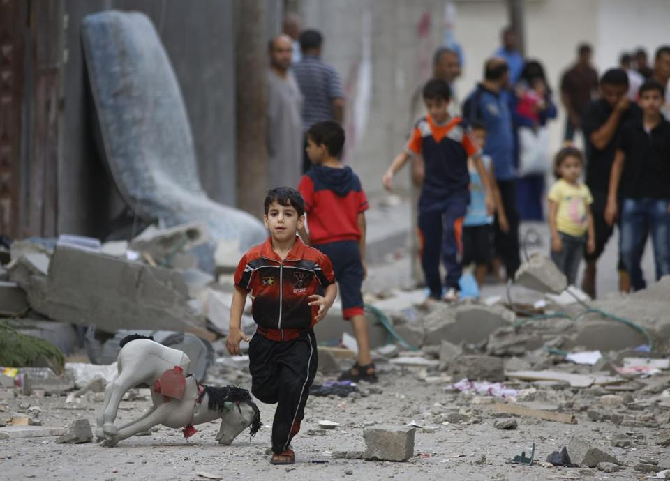 A Palestinian child runs on debris from a house that was destroyed Saturday in an Israeli strike in Beit Lahiya, Gaza Strip. AP Photo/Lefteris Pitarakis