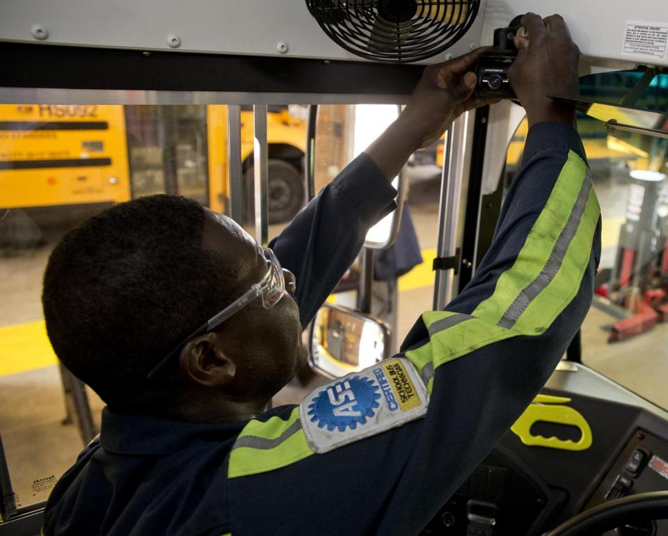 Andrew Prince, a technician with the Boston School Department, installed a video camera in one of the school buses that will be used this fall.