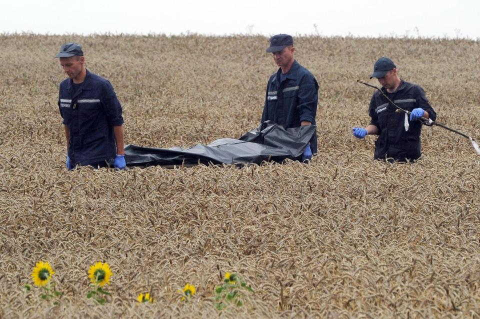 Workers carried the body of a Malaysia Airlines Flight 17 crash victim on a stretcher on Saturday.