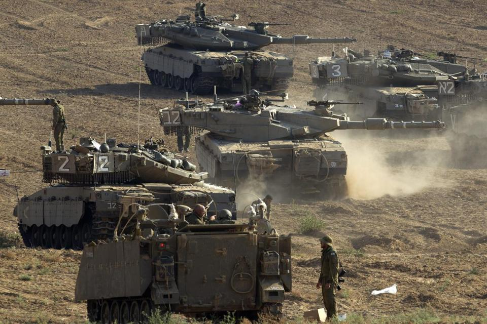 Israeli tanks and armored personnel carriers were held in a staging area close to the border.