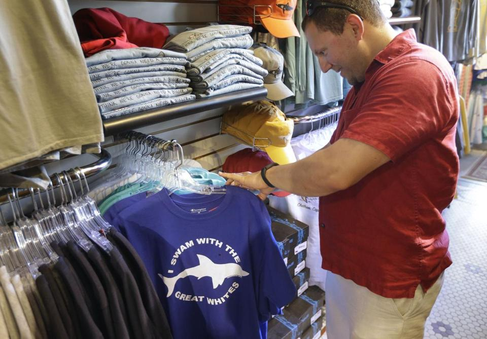Mark McCurdy of Everett examined shark-themed clothing at the Chatham Clothing Bar. Growing sightings of great white sharks off Cape Cod are generating extra business.