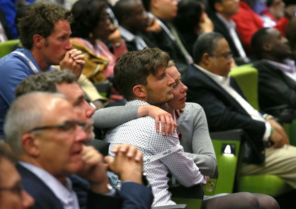 At the International AIDS Conference in Melbourne, participants comforted each other as they remembered colleagues killed aboard Malaysian Airlines flight MH17.