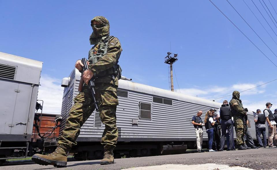 Rebels guarded a train station in Torez as OSCE inspectors waited for the doors of the trains carrying bodies to open.