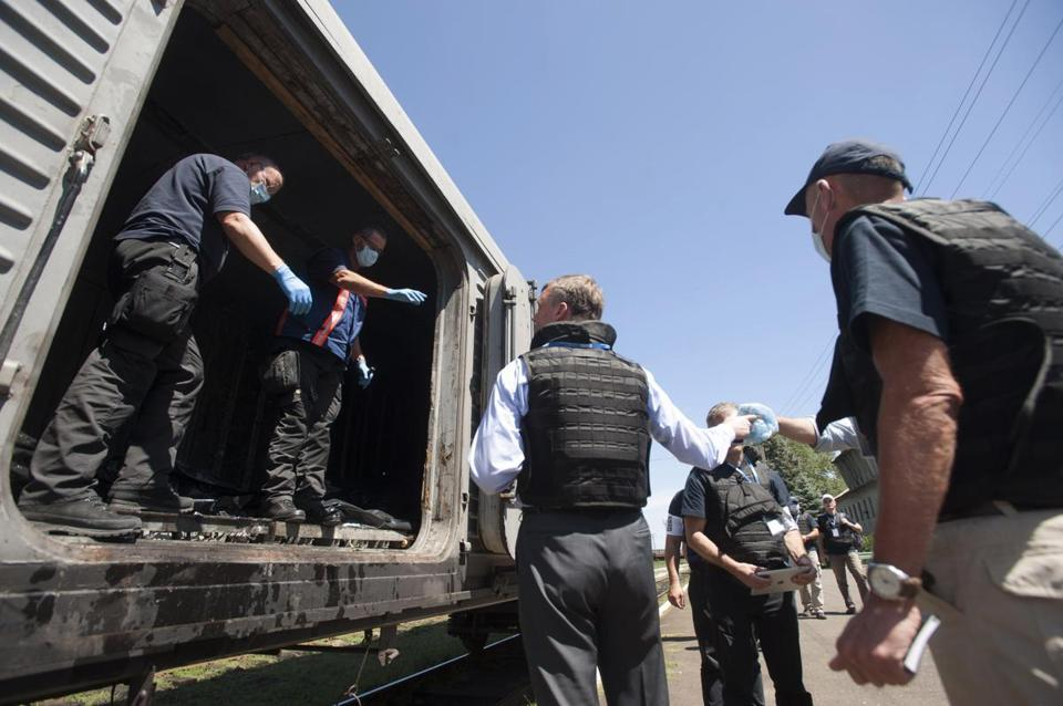 Alexander Hug, center, who is deputy head of the OSCE mission, spoke to a member of the Netherlands' National Forensic Investigations Team as a refrigerated train loaded with bodies of the passengers departed.