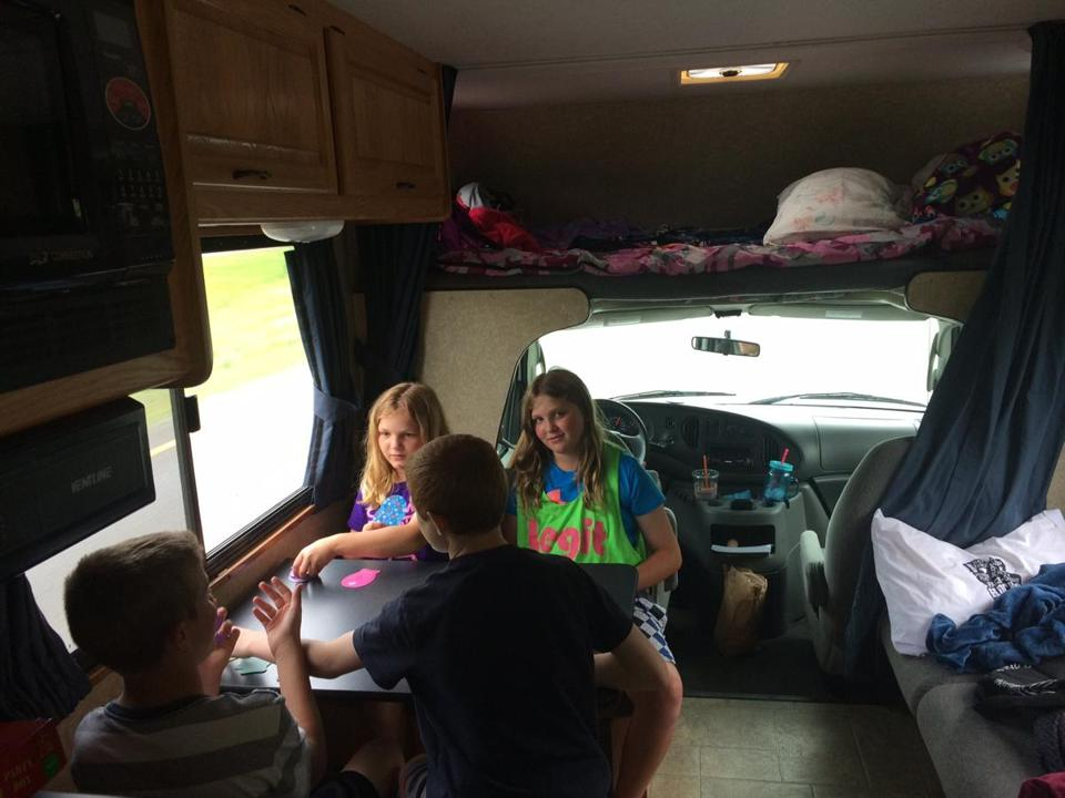 "Our rental RV in Tyngsborough was an eye-catching ad for Cruise America. On the road, the kids' card game of choice was ""Go Fish."" The  compartment above the driver's seat was big enough for the two girls."